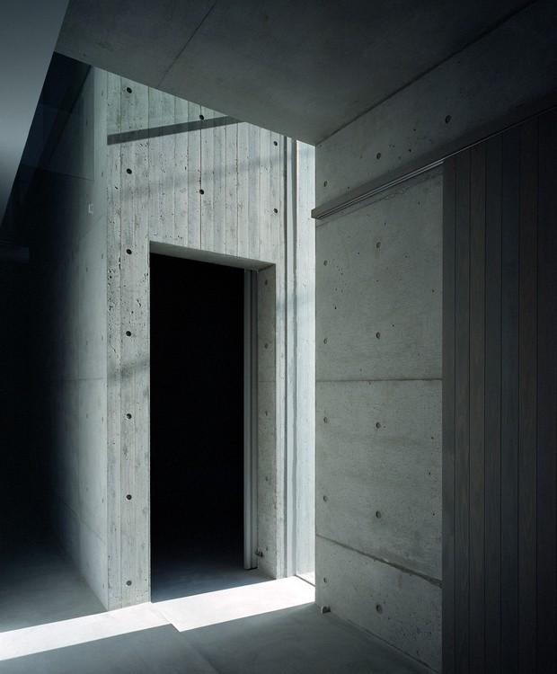 O interior tem aparência fria devido ao concreto. O vão de claridade aparece para aquecer e provocar efeitos estratégicos de luz e sombra  (Foto:  Katsuya Taira/Studio Rem/ Deezen / Reprodução)