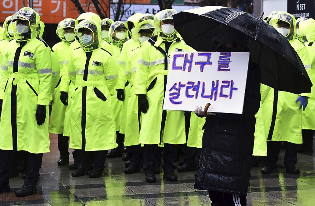 Manifestante segura cartaz que diz 'salve Daegu' em Daegu, na Coreia do Sul, onde foi registrado o maior número de casos do novo coronavírus no país, nesta terça-feira (25). — Foto: Lee Moo-ryul/Newsis via AP