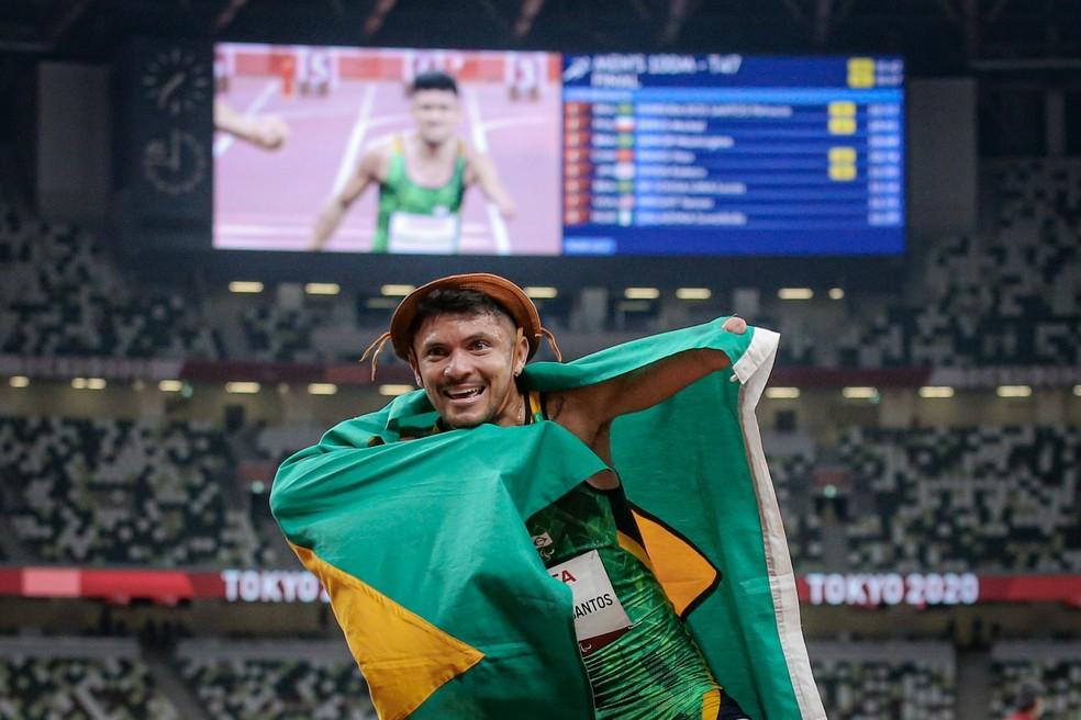 Petrúcio Ferreira comemora com chapéu de couro e bandeira do Brasil o título dos 100m T47 — Foto: Wander Roberto /CPB @wander_imagem