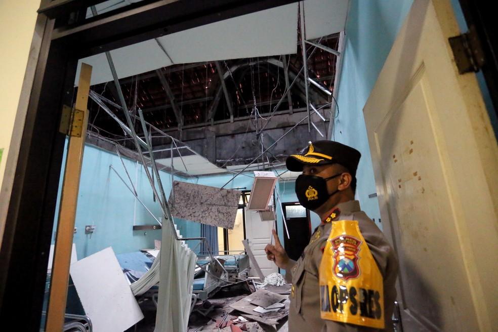 Policial observa hospital danificado por terremoto neste sábado (10) em Blitar, na Indonésia — Foto: Reuters/Antara Foto/Irfan Anshori