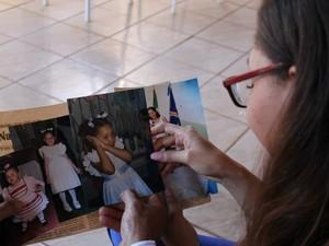 Aline recorda de fotos de quando era criança (Foto: Maria Caroline Palieraqui/G1 MS)