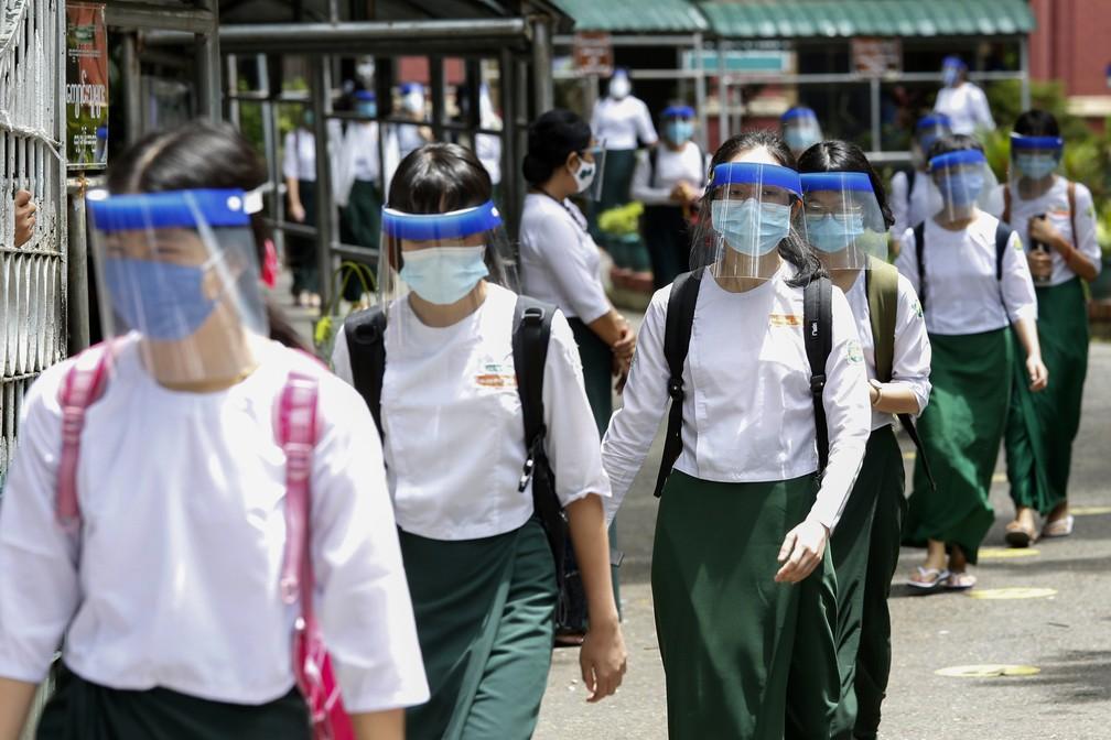 Estudantes voltam às aulas com máscaras e escudos faciais em Rangun, Mianmar, para se protegerem contra a Covid-19 no dia de reabertura das escolas públicas, nesta terça (21). — Foto: Sai Aung Main / AFP