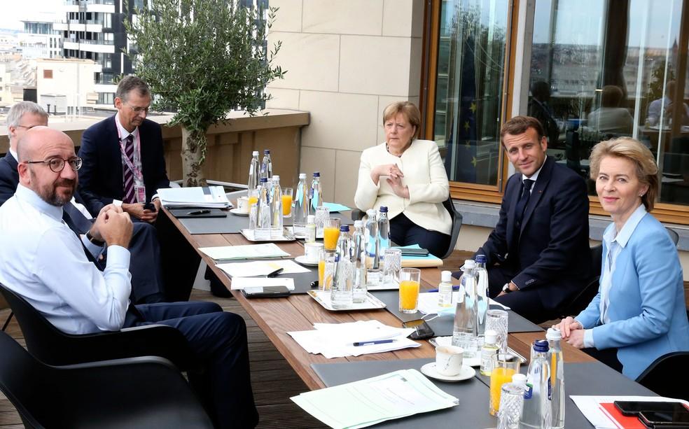 À esquerda, presidente do Conselho Europeu, Charles Michel, participa neste domingo (19) de reunião à margem do encontro de cúpula da União europeia com a chanceler Angela Merkel (Alemanha), o presidente Emmanuel Macro (França) e a presidente da Comissão Europeia, Ursula von der Leyen — Foto: Francois Walschaerts/AP