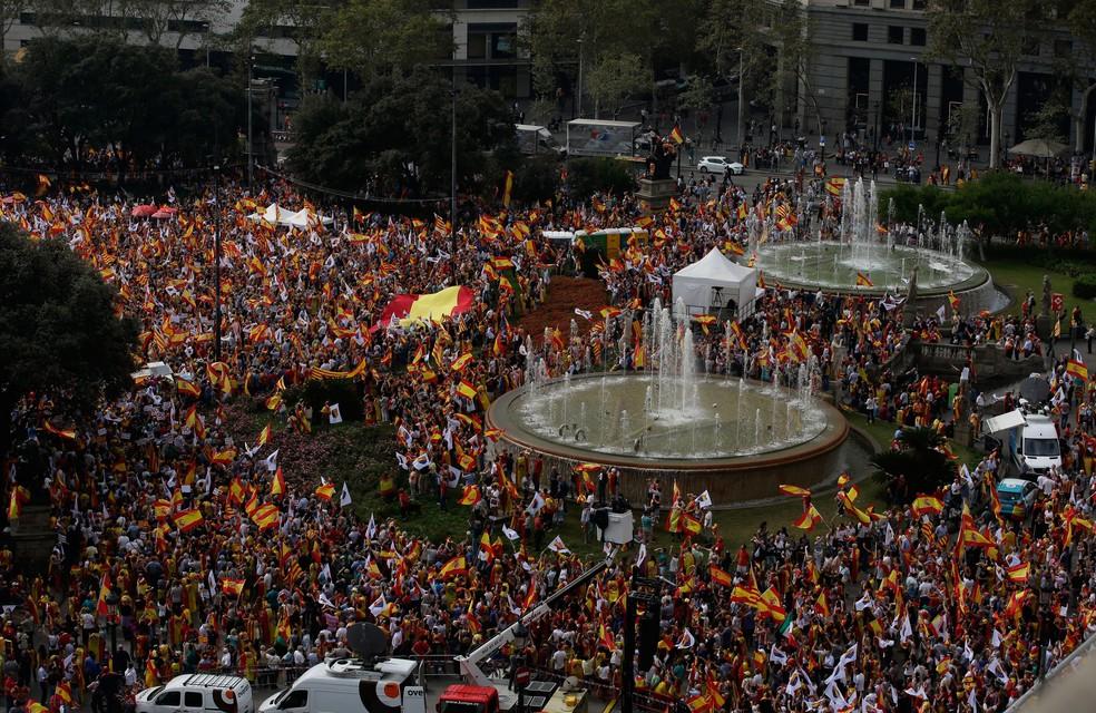 Manifestantes carregam bandeiras catalãs e espanholas enquanto celebram o feriado conhecido como