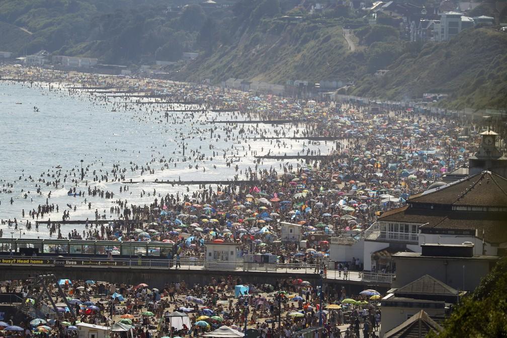 Milhares de pessoas se aglomeram em praia de Bournemouth, cidade no sul da Inglaterra, nesta quarta-feira (24) — Foto: Andrew Matthews/PA via AP