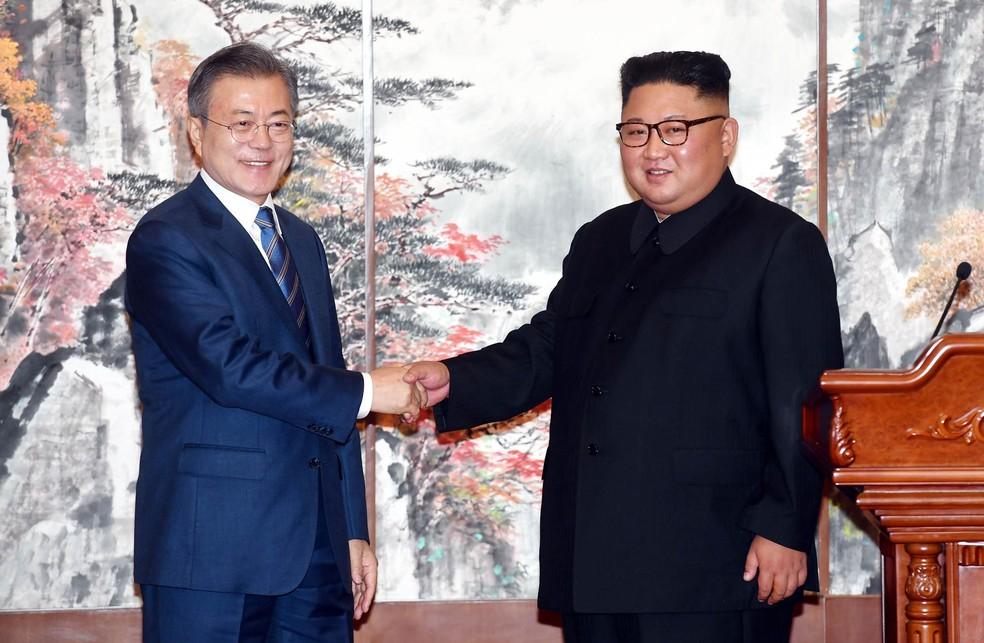 O presidente sul-coreano Moon Jae-in (esq.) e o líder norte-coreano Kim Jong-un apertam as mãos durante encontro em Pyongyang, na Coreia do Norte. Novos acordos da reaproximação incluem o fechamento do sítio norte-coreano de testes de mísseis de Tongchang-ri, a redução da possibilidade de confrontos entre seus exércitos ao redor da fronteira que compartilham, e uma candidatura conjunta aos Jogos Olímpicos de 2032 — Foto: Pyongyang Press Corps Pool via AP