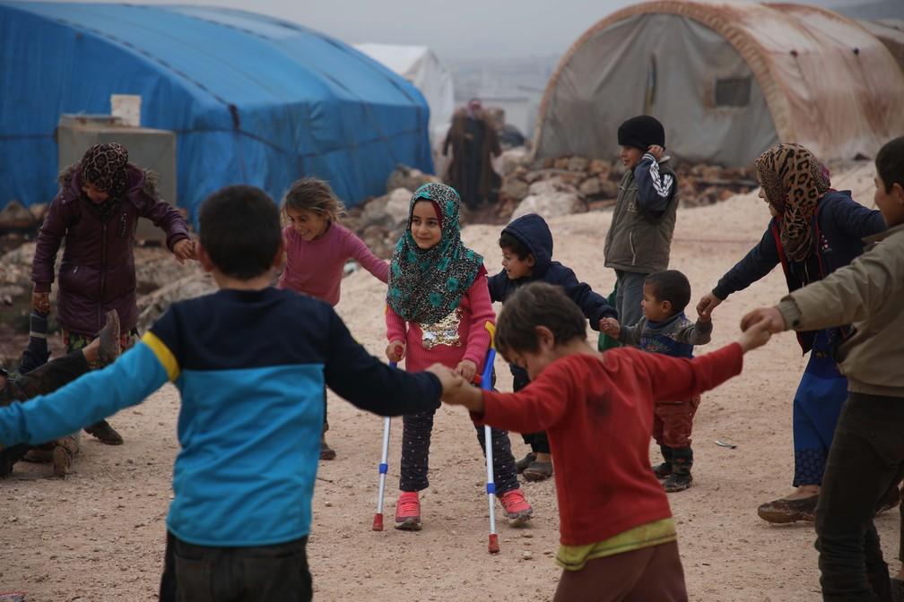 Menina síria Maya Merhi é clicada brincando com outras crianças após aprender a andar com próteses — Foto: Aaref Watad/AFP