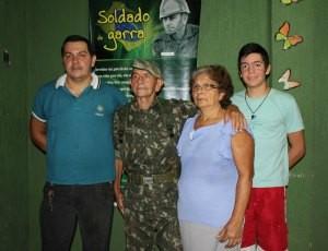Parte da família do sargento. Do lado esquerdo o filho Aureo Júnior, do lado direito o neto que quer serguir os passos do avó. O baner ao fundo foi presente de aniversário (Foto: Ivanete Damasceno/G1)