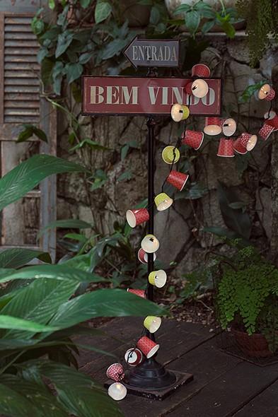 Uma plaquinha no quintal mostra que a entrada está próxima. Repare no detalhe do pisca-pisca, feito com copos de papel