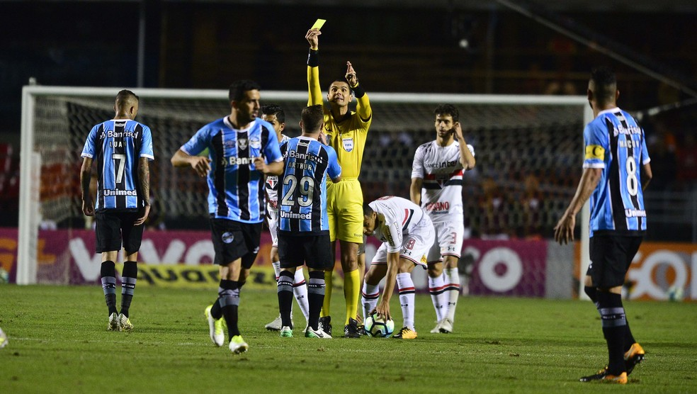 Ricardo Marques Ribeiro mostra o amarelo para Arthur, do Grêmio, em jogo contra o São Paulo (Foto: Marcos Ribolli)
