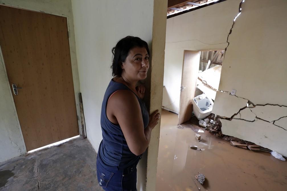 Isamara de Araújo em pé dentro de casa, que foi parcialmente destruída depois do rompimento da barragem da Vale em Brumadinho. — Foto: André Penner/AP