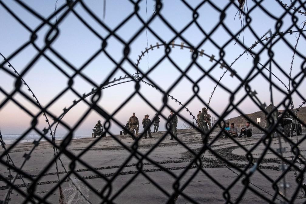 Migrantes da América Central - viajando em uma caravana ao lado de policiais de patrulha de fronteira dos EUA após atravessarem a cerca da fronteira do México com o Condado de San Diego — Foto: Guillermo Arias / AFP