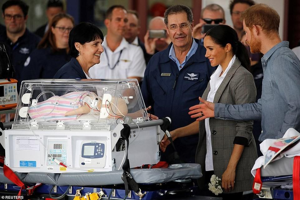Casal observa o boneco de um bebê em uma incubadora (Foto: Reprodução Daily Mail)