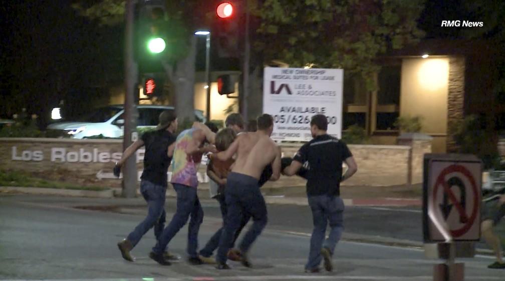 Vítima de tiroteio em casa noturna é carregado na noite desta quarta-feira (7) em Thousand Oaks, na Califórnia — Foto: RMG News via AP