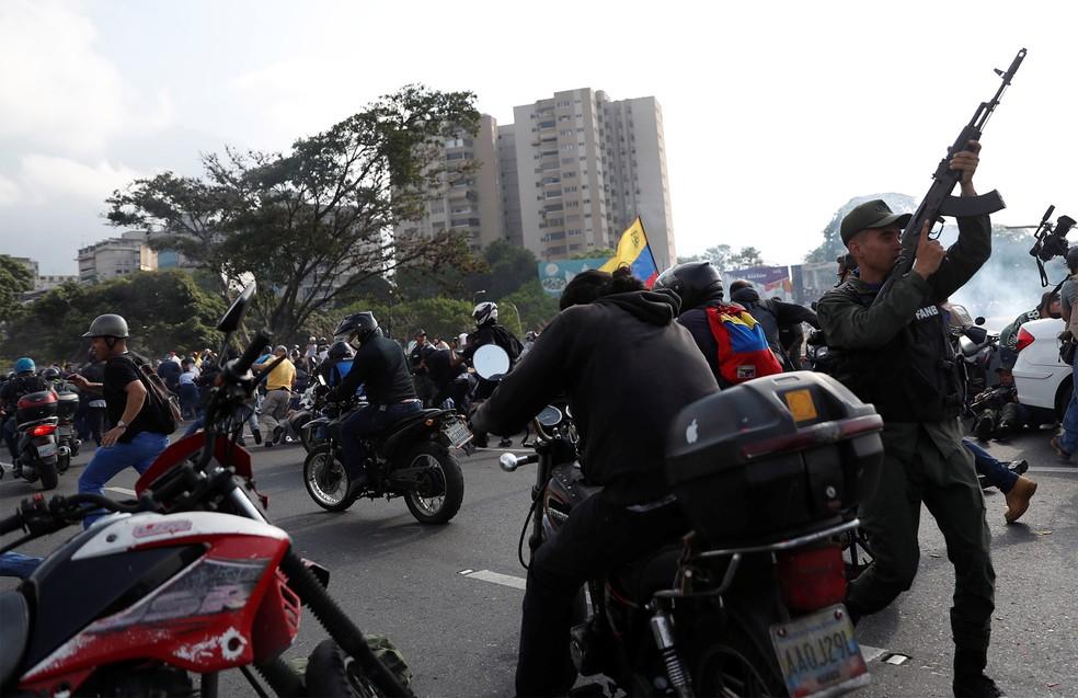 Soldados e civis apoiadores de Juan Guaidó reagem ao som de tiros perto da base aérea Generalísimo Francisco de Miranda, conhecida como 'La Carlota', em Caracas — Foto: Carlos Garcia Rawlins/Reuters
