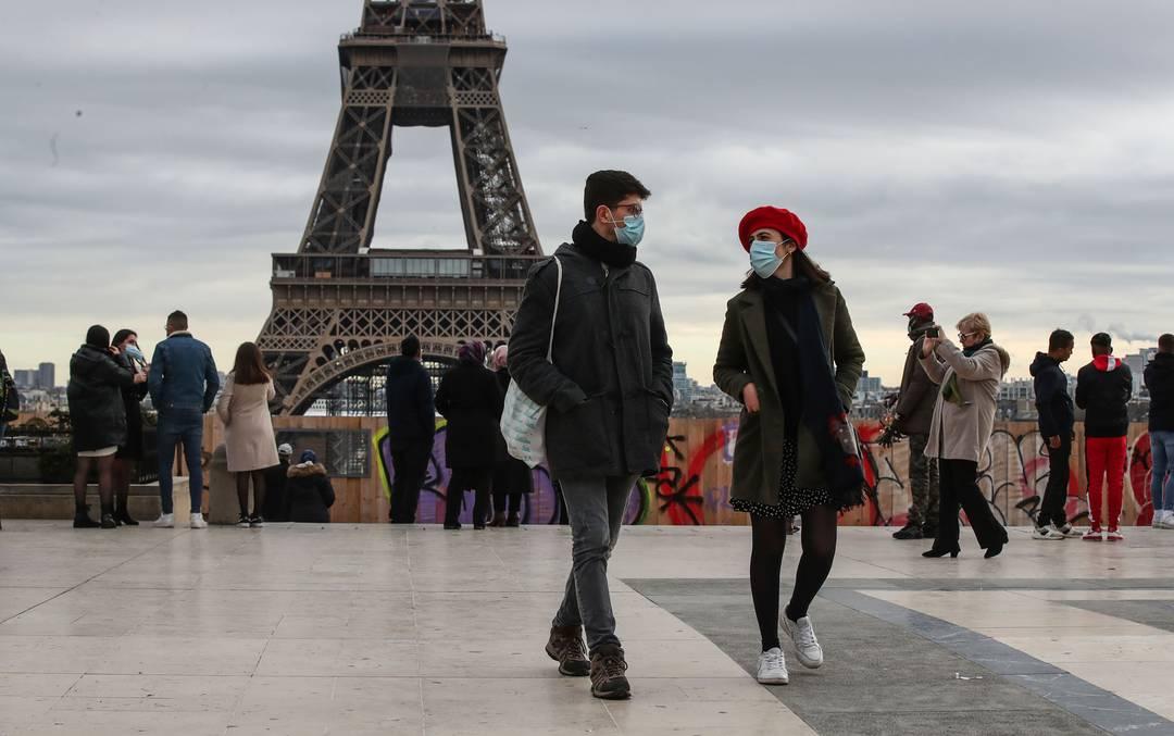 Pessoas usando máscaras são vistas caminhando perto da Torre Eiffel, em Paris, em 26 de dezembro