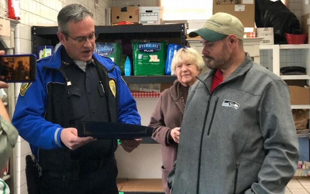 O chefe de polícia Brad Moericke entrega homenagem a Kevin Booth no Sumner Food Bank, em Washington — Foto: NBC