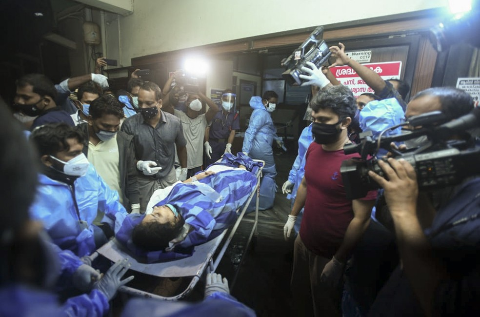 Uma das pessoas feridas após voo da Air India Express derrapar durante pouso no aeroporto de Calicute é levada para tratamento no Medical College Hospital em Calicute, Kerala, Índia — Foto: AP Photo