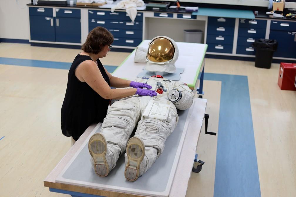 Lisa Young, restauradora do Museu Nacional do Ar e do Espaço Smithsonian ajusta traje usado por Armstrong quando o astronauta esteve na Lua em 1969. — Foto: Kevin Fogarty/Reuters