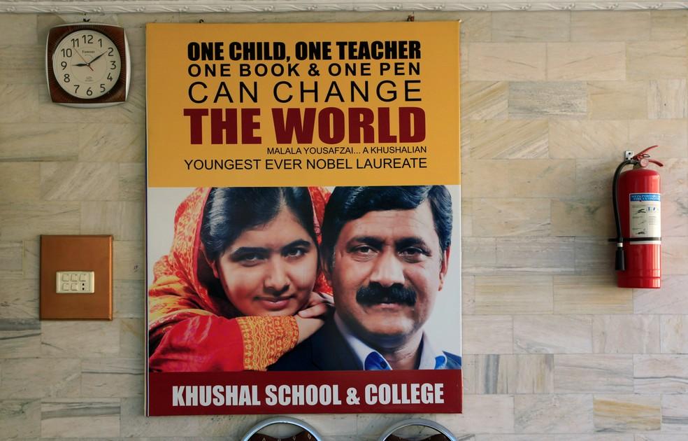 Cartaz com Malala e seu pai, Ziauddin Yousufzai, é exibido na parede da Escola Khushal, localizada na cidade Natal de Malala  — Foto: Faisal Mahmood/Reuters