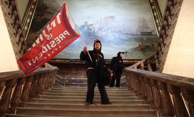 Apoiador de Trump levanta bandeira a favor de presidente dentro do Capitólio, após invasão