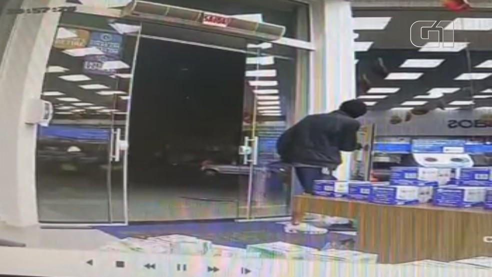 Assaltante passou álcool em gel antes de roubar farmácia — Foto: Polícia Civil