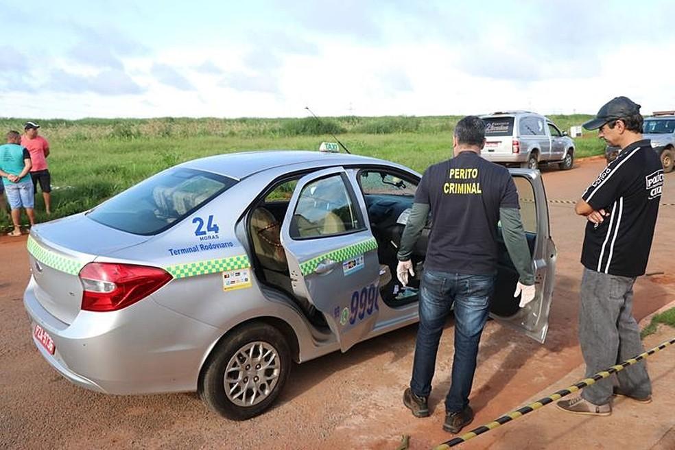 Peritos e policiais analisam o carro do taxista assassinado em Nova Mutum — Foto: Djeferson Kronbauer/Power Mix
