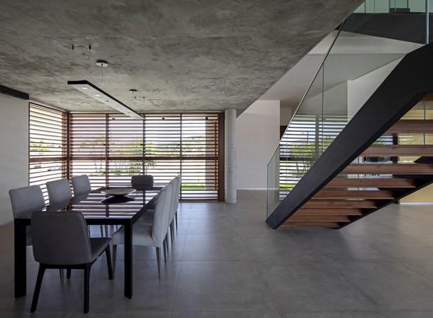 A área social no pavimento térreo é completamente integrada. Esquadrias de vidro da Estrutural separam área externa com piscina.  (Foto: Maíra Acayaba/Divulgação)