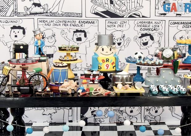 A mesa — Destaque para os quadrinhos em preto e branco que fazem as vezes de painel. As cores vermelho, amarelo e azul das bandejas contrastaram com o preto laqueado da mesa, valorizando a decoração. E não poderia faltar a famosa panela que o personagem u (Foto: Thaís Galardi)