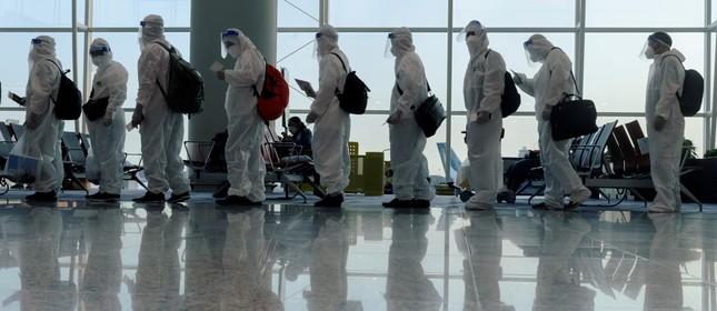 Passageiros vestindo roupas de proteção fazem fila para embarcar em voo internacional no aeroporto de Hong Kong, China