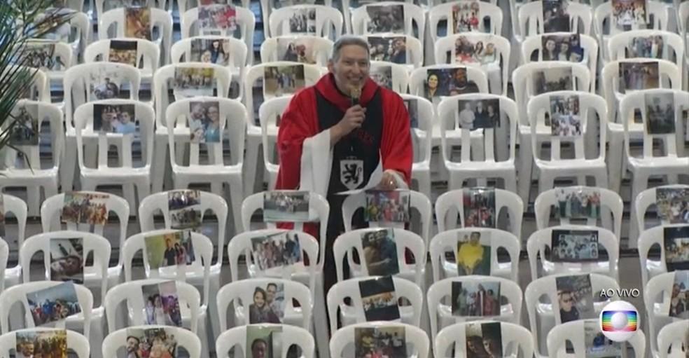 Padre Marcelo Rossi durante missa no Santuário Mãe de Deus neste domingo (5): cadeiras ocupadas com fotos de profissionais de saúde  — Foto: Reprodução/TV Globo