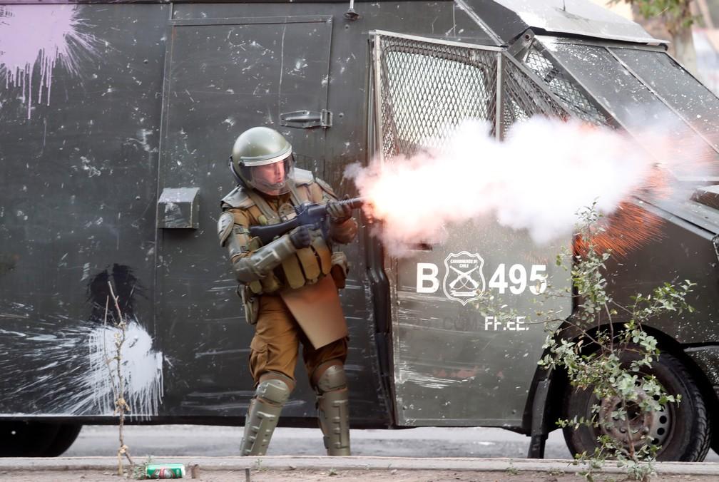 Policial atira bomba de efeto moral em protesto em Santiago, no Chile, nesta quinta-feira (14) — Foto: Goran Tomasevic/Reuters