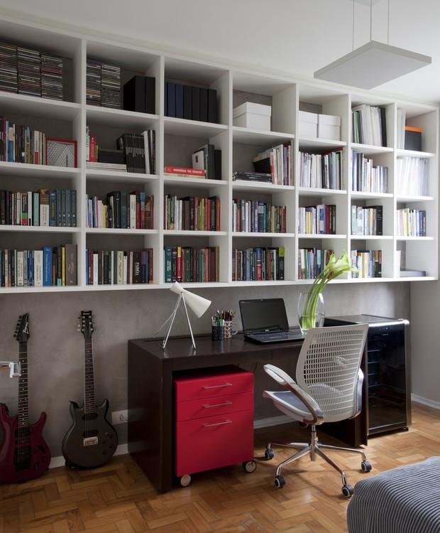 No escritório, foi usado bricolagem na parede, imitando cimento queimado. A estante e a escrivaninha foram desenhadas pela arquiteta e executadas pela Móveis Russo. O gaveteiro vermelho e a cadeira são da Tok & Stok e a luminária é La Lampe  (Foto: Marco Antonio)