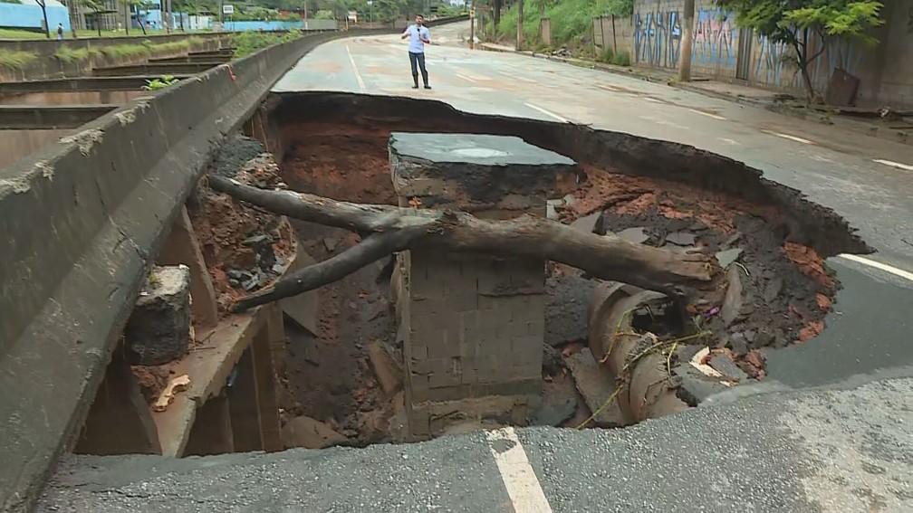 Repórter Danilo Girundi mostra cratera que se abriu na Avenida Tereza Cristina, na Região Oeste de BH — Foto: Reprodução/TV Globo