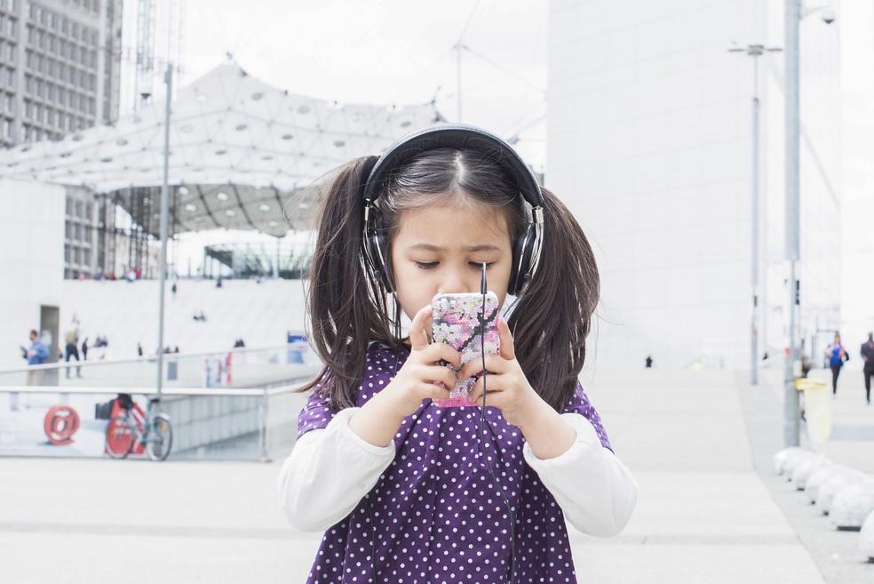 -HN- Criança mexe em um smartphone enquanto ouve música com fones de ouvido; celular — Foto: Anne-Sophie Bost/AltoPress/PhotoAlto