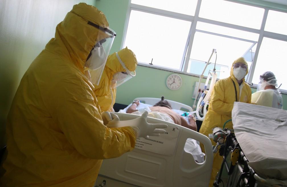 12 de maio - Enfermeiros do SAMU (Serviço de Atendimento Móvel de Urgência) se preparam para transportar paciente de um centro de saúde de emergência para hospital, em meio à pandemia de coronavírus (COVID-19), em Santo André, São Paulo — Foto: Rahel Patrasso/Reuters