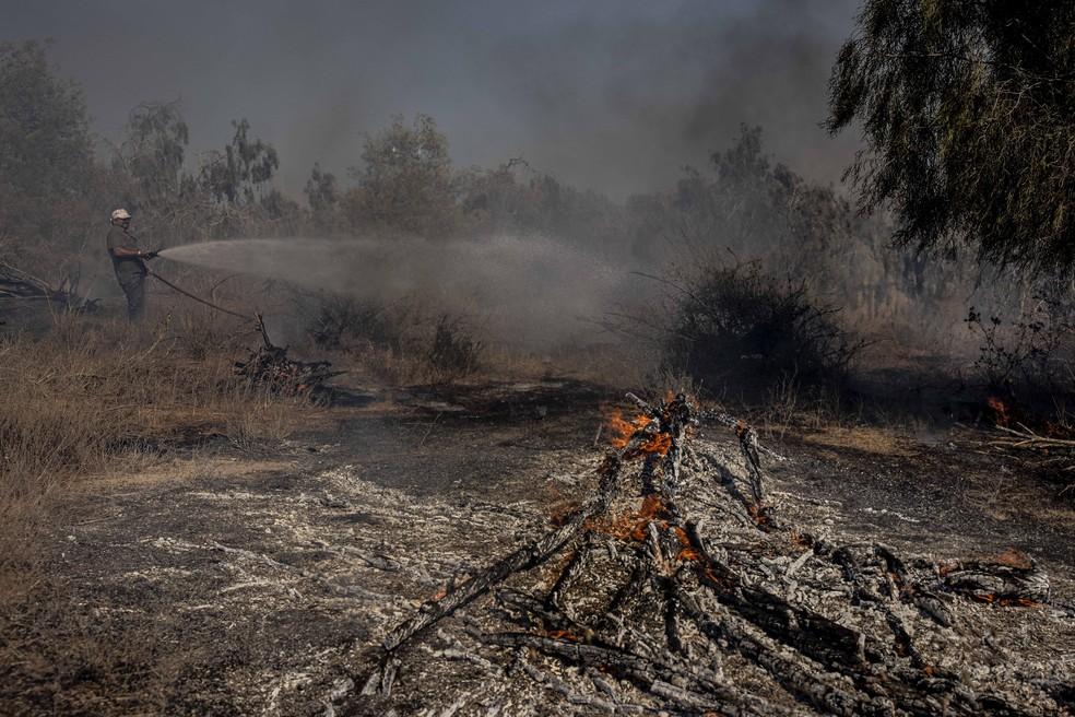 Um bombeiro israelense tenta apagar um incêndio causado por um balão incendiário lançado por palestinos na Faixa de Gaza, no lado israelense da fronteira entre Israel e Gaza, no domingo (16) — Foto: Tsafrir Abayov/AP