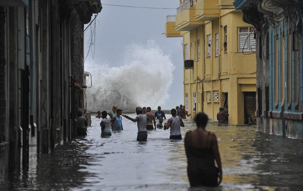 Moradores atravessam rua alagada enquanto, ao fundo, uma onda explode na costa em Havana, Cuba, no domingo (10) (Foto: Yamil Lage/AFP)