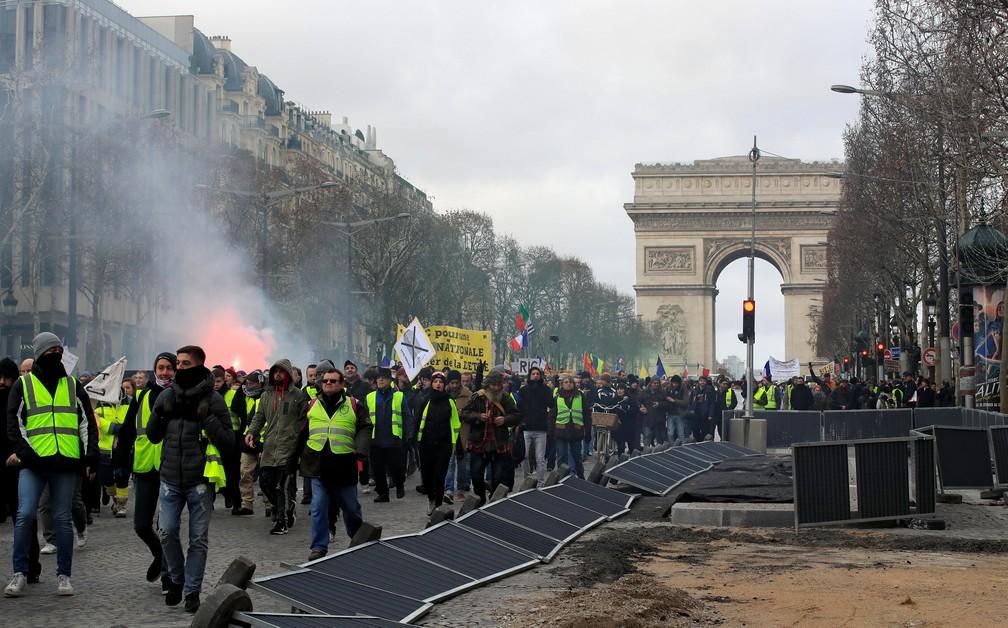 """Manifestantes se reúnem no Arco do Triunfo, em Paris, no 13º sábado de protestos dos """"coletes amarelos"""". — Foto: Gonzalo Fuentes/Reuters"""