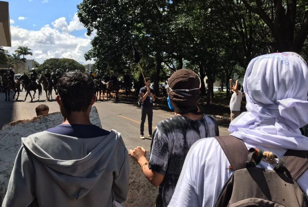 Manifestantes da Universidade de Brasília enfileirados na via de acesso ao Ministério da Educação, em frente à cavalaria da Polícia Militar (Foto: Luiza Garonce/G1)