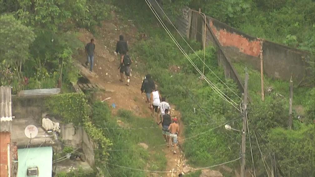 Criminosos, alguns armados com pistolas e fuzis, buscam abrigo na mata no Morro Camarista Méier (Foto: Reprodução/ TV Globo)