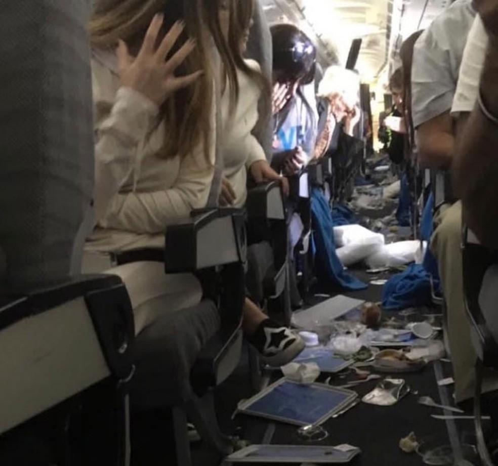 Passageiros observam objetos espalhados no chão de avião da Aerolineas Argentinas após forte turbulência em voo entre Miami e Buenos Aires, na quinta-feira (18) — Foto: Reprodução/Twitter/Martin Narducci