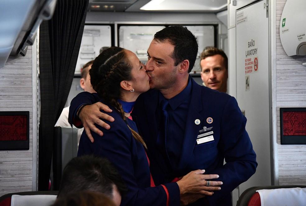 Comissários de bordo se beijam após Papa Francisco celebrar o casamento durante voo no Chile, nesta quinta-feira (18)  (Foto: Vincenzo Pinto /Reuters)