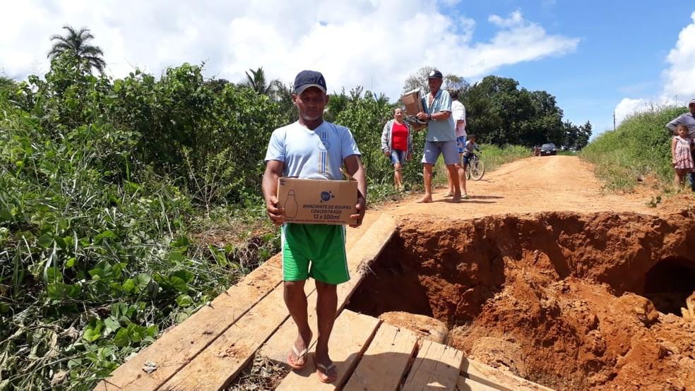 Moradores se arriscam para passar pelas pontes danificadas para repor os mantimentos — Foto: Luiz Martins/Rede Amazônica