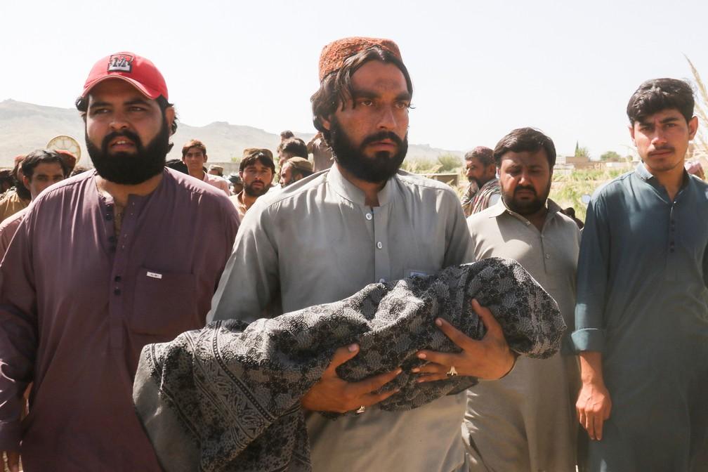 Homem carrega o corpo de uma criança que morreu no terremoto em Harnai, na província do Baluchistão, durante funeral em 7 de outubro de 2021 no Paquistão — Foto: Naseer Ahmed/Reuters