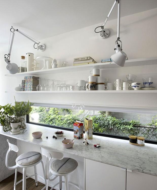 Na cozinha, prateleiras e armários nas paredes aproveitam o espaço para garantir locais de armazenamento (Foto: Indecora/ Reprodução)