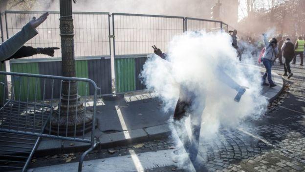 Em Paris, a polícia usou gás lacrimogêneo para dispersar manifestantes (Foto: EPA/BBC)