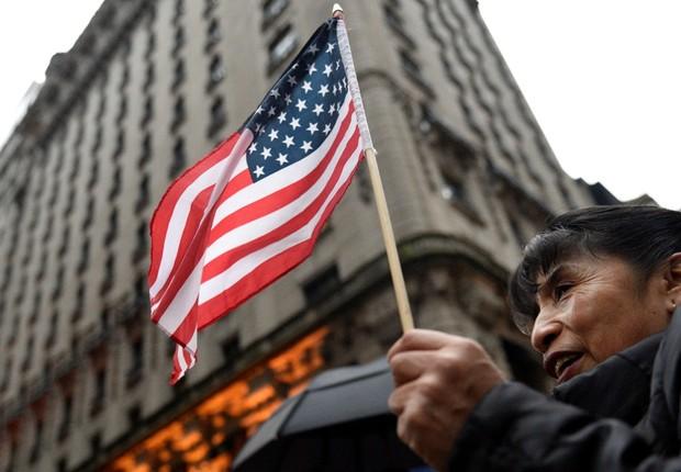Mulher segura bandeira dos Estados Unidos diante da Trump Tower em Nova York (Foto: Darren Ornitz/Reuters)