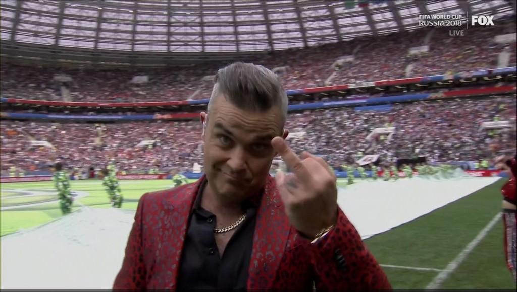 O cantor Robbie Williams mostrando o dedo para uma câmera durante o show de abertura da Copa 2018 (Foto: Reprodução)