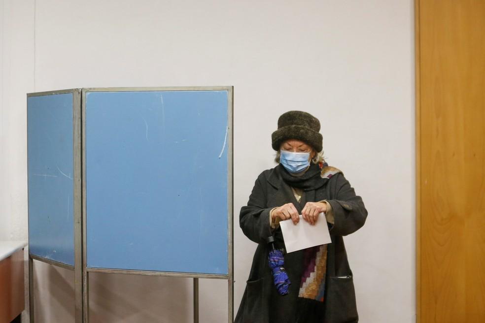 Mulher de máscara segura cédula de votação em seção eleitoral em Lisboa — Foto: Pedro Nunes/Reuters
